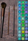 Комплект щеток и тени глаза на деревянной предпосылке стоковые фотографии rf