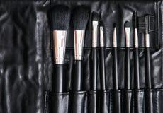 Комплект щеток косметики в черной кожаной сумке, забота кожи Стоковые Изображения