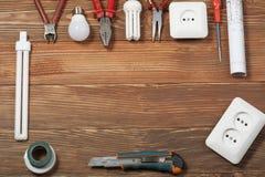 Комплект электрического инструмента на деревянной предпосылке Аксессуары для инженерных работ, концепции энергии Стоковая Фотография RF
