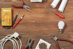 Комплект электрического инструмента на деревянной предпосылке Аксессуары для инженерных работ, концепции энергии Стоковое Изображение