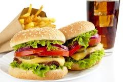 Комплект 2 cheeseburgers, французских фраев, стекла колы на плите Стоковое Изображение RF