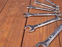 Комплект wrenchs покрывает хромом аппаратуры гаечного ключа металла на деревянной поверхности Стоковая Фотография