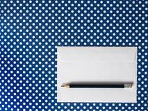 Конверт белой бумаги и черный карандаш на голубой польке предпосылки Стоковая Фотография RF