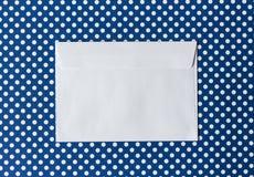 Конверт белой бумаги на голубой точке польки предпосылки в cente Стоковое фото RF