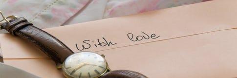 Конверт пастельного цвета с античными наручными часами на шелковистой ткани, романтичной любовью стоковое изображение