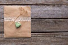 Конверт с белой лентой и сердце на деревянной предпосылке Стоковая Фотография
