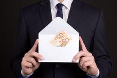 Конверт с деньгами в руках бизнесмена Стоковые Изображения