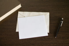 Конверт с письмом на деревянном столе Около книги и ручки Стоковые Фото