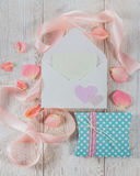 Конверт с письмом, розовой лентой и подарками на деревянной предпосылке Стоковое фото RF