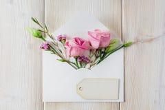 Конверт с цветками на деревянной предпосылке Стоковая Фотография