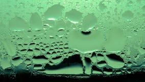 Конденсация, пар, дождь, падения воды различных размеров на стеклянной поверхности Зеленый цвет тона стоковое изображение