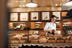 кондитерская Женщина продавая конфеты шоколада в магазине стоковая фотография rf