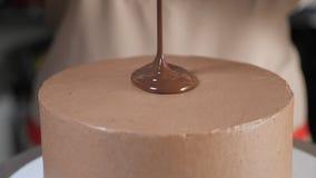 Кондитер льет жидкостный шоколад на верхней части торта для того чтобы украсить его акции видеоматериалы