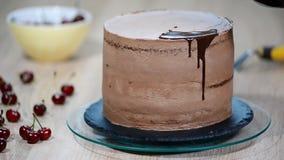 Кондитер льет шоколад на торте видеоматериал