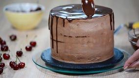 Кондитер льет шоколад на торте акции видеоматериалы