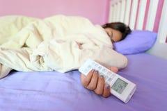 Кондиционер владением руки молодой женщины удаленный и спать в стоковое фото rf
