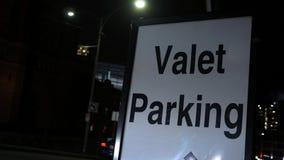 Конец вверх автостоянки слуги подписывает внутри район центра города на ноче видеоматериал