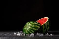 Конец-вверх арбуза отрезка круглого зрелого на черной предпосылке Освежающе сладостная ягода с малыми черными семенами на поверхн Стоковые Изображения