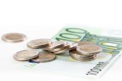 Конец-вверх 100 банкноты евро и евро чеканит на задней части белизны Стоковые Фотографии RF
