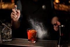 Конец-вверх бармена делая коктейль алкоголя используя спрейер стоковое фото rf