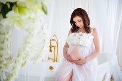 Конец-вверх беременной девушки в красивом интерьере с цветками Стоковая Фотография RF