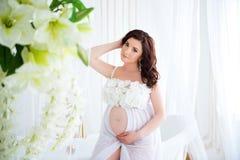 Конец-вверх беременной девушки в красивом интерьере с цветками Стоковые Изображения