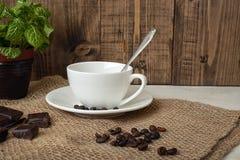 Конец-вверх белых чашки и кофейных зерен с шоколадом на таблице Стоковая Фотография RF