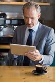 Конец-вверх бизнесмена используя цифровую таблетку в café Стоковые Изображения