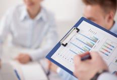 Конец-вверх бизнесмена объясняя финансовый план к коллегам на встрече Стоковые Изображения