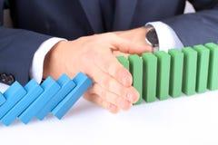 Конец-вверх бизнесмена останавливая влияние домино с рукой Стоковые Изображения