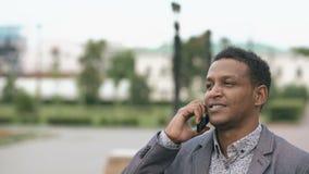 Конец-вверх бизнесмена смешанной гонки вызывая мобильный телефон outdoors