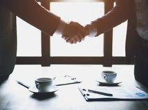 конец вверх 2 бизнесмена тряся руки в кафе Стоковые Изображения