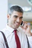 Конец-вверх бизнесмена усмехаясь на мобильном телефоне Стоковая Фотография