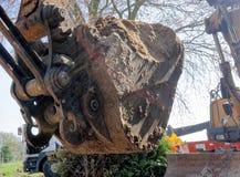 Конец-вверх большого ковша экскаватора заполнил с могущественной нагрузкой свободного коричневого песка на строительной площадке Стоковая Фотография