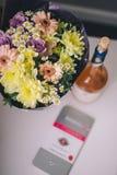 Конец-вверх букета красочных цветков в пурпурных упаковывая стойках, розовое вино и роскошный шоколад на белой таблице стоковая фотография rf