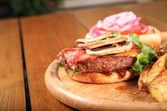 Конец вверх бургера бекона на плите Стоковое Изображение