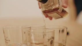 Конец-вверх бутылки алкоголя Алкоголь полил от бутылки в стекло красивая крутая рамка Кинематографический сток-видео