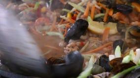 Конец вверх варя морепродукты saute тушёное мясо в сковороде сток-видео