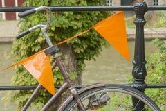 Конец вверх велосипеда украшенного с оранжевыми флагами Стоковое Фото