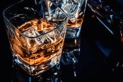 Конец-вверх верхней части взгляда стекла вискиа около бутылки на черной таблице с отражением, старым стилем Стоковое Изображение