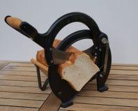 Конец-вверх винтажного датского slicer хлеба с датским белым хлебом стоковое изображение