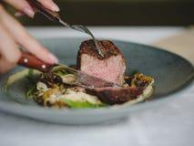 Конец-вверх вкусного блюда в голубой плите на белой предпосылке таблицы Рука режет часть мяса скопируйте космос стоковое фото