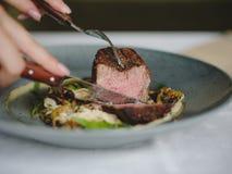 Конец-вверх вкусного блюда в голубой плите на белой предпосылке таблицы Рука режет часть мяса скопируйте космос стоковые изображения rf