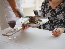 Конец-вверх вкусного блюда в голубой плите рядом с комплектом обедающего на темной предпосылке деревянного стола скопируйте космо стоковое изображение rf