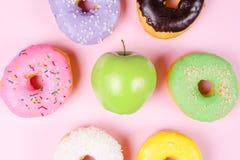 Конец-вверх вкусных donuts и свежего зеленого яблока на розовой предпосылке предлагая здоровую концепцию еды Стоковые Фото