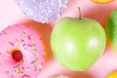 Конец-вверх вкусных donuts и свежего зеленого яблока на розовой предпосылке предлагая здоровую концепцию еды Стоковое Изображение RF