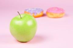 Конец-вверх вкусных donuts и свежего зеленого яблока на розовой предпосылке предлагая здоровую концепцию еды Стоковая Фотография