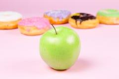 Конец-вверх вкусных donuts и свежего зеленого яблока на розовой предпосылке предлагая здоровую концепцию еды Стоковое Фото