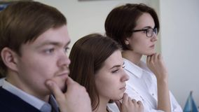 Конец-вверх внимательного конторского персонала Команда совместно думает о том, как разрешить задачу 3 работника офиса на таких ж сток-видео
