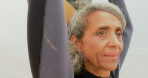 Конец-вверх внимательной активной старшей Афро-американской женщины с положением surfboard на пляже 4k акции видеоматериалы